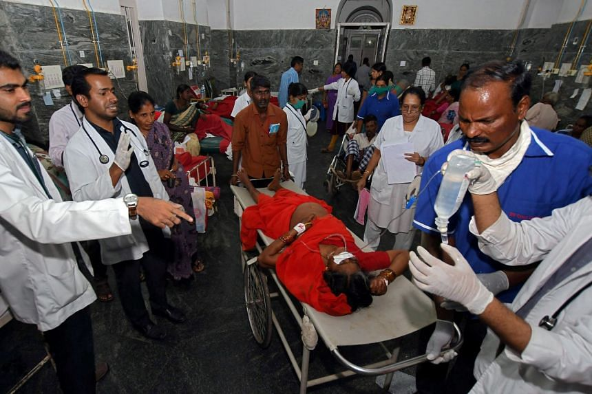 Medics tend to people who hospitalised after the poisoning incident in Mysuru, India.