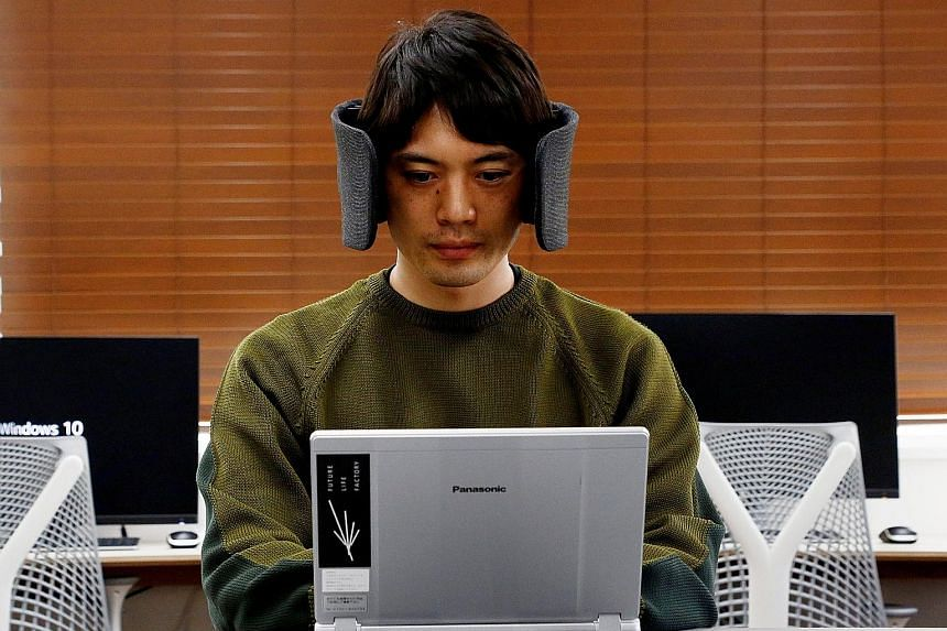 "A designer at Panasonic wearing a prototype of ""Wear Space"", a headset that limits noise and peripheral vision."