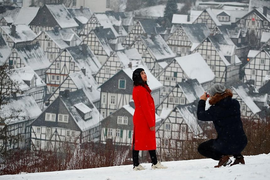 """A couple taking photographs against the backdrop of snow-covered roofs in the so-called """"Alter Flecken"""", or """"old spot"""", the historic core of downtown Freudenberg. The German town is located in the heart of the federal state of North Rhine-Westphalia,"""