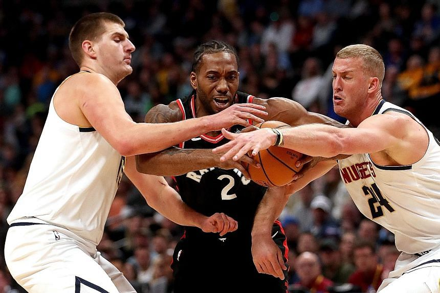 The Toronto Raptors' Kawhi Leonard is closely marked by the Denver Nuggets' Nikola Jokic (left) and Mason Plumlee while driving to the basket in the first quarter of Denver's 95-86 home win on Sunday. Victory over the league-leading Raptors helped th