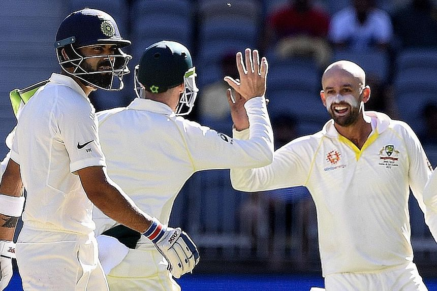 India captain Virat Kohli (left) is dismayed after being dismissed by Australian bowler Nathan Lyon for 17 runs on day four of the second Test match between Australia and India at Perth Stadium yesterday. Australia are poised for their first Test vic