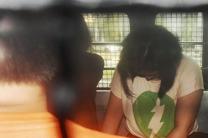 One of the four shoplifters in a police van. She and three other Vietnamese stole more than 1,400 items from various Uniqlo stores.