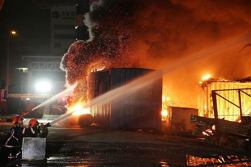 SCDF firefighters battling a blaze at 31 Sungei Kadut Street 2 in the early hours of yesterday morning. At the height of operations, 12 water jets were used to bring the fire under control.