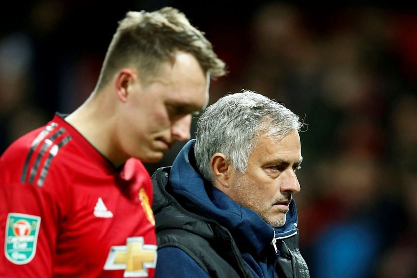 Manchester United's Phil Jones and former manager Jose Mourinho look dejected after Derby County win the penalty shootout during the third round of the Carabao Cup on Sept 25, 2018.