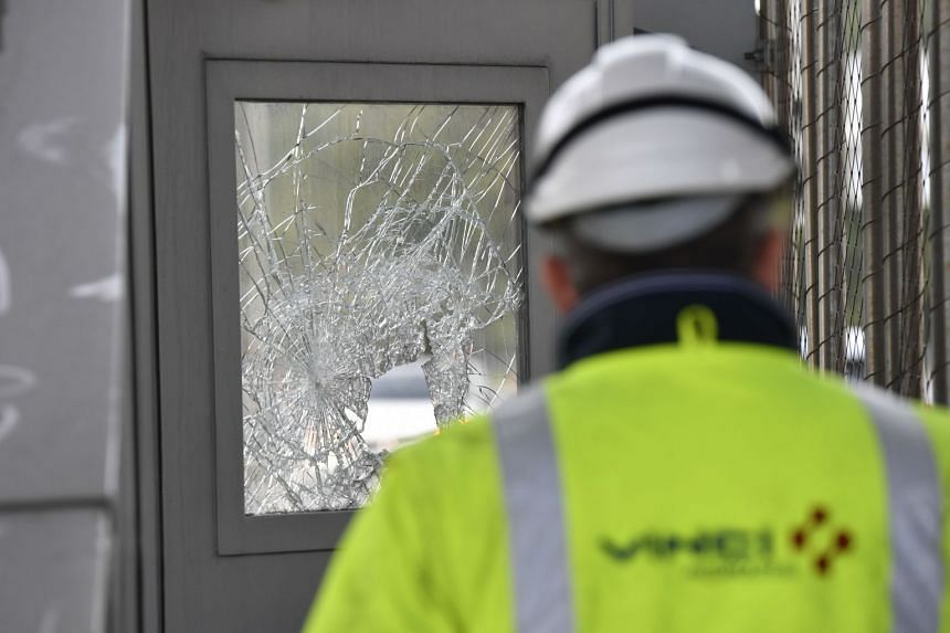 A Vinci worker stands near a broken window a day after the highway toll was set on fire in Bandol, near Marseille.