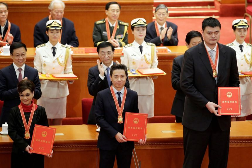 (From left) Chinese singer Li Guyi, Baidu CEO Robin Li and retired basketball player Yao Ming holding their certificates at a ceremony held at the Great Hall of the People to mark the 40th anniversary of China's reform and opening up.