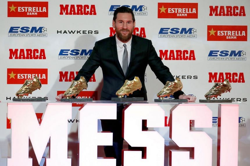 Messi poses after receiving his fifth Golden Boot trophy.