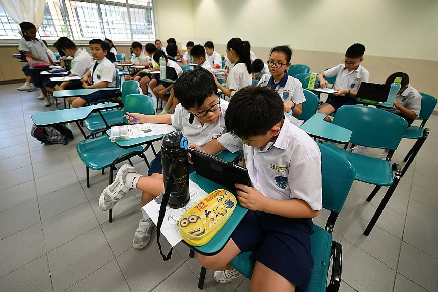 Primary 4 pupils at Bedok Green Primary School reading information about the different parts of a plant via an app during a lesson on plant diversity.