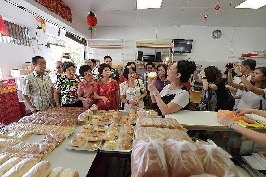 Participants taking in the strong aroma of freshly baked bread at Sweetlands Confectionery and Bakery yesterday in Kim Keat Lane, where they learn the process of making bread the old-fashioned way. The stretch of Sim Kwong Ho shophouses in Balestier