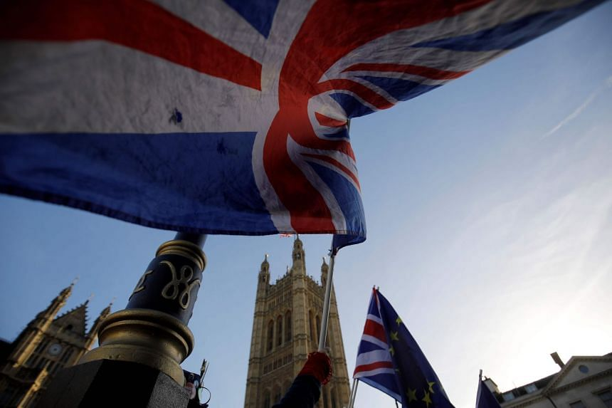 Anti-Brexit campaigners wave the Union and EU flags outside the Houses of Parliament in central London, on Dec 17, 2018.