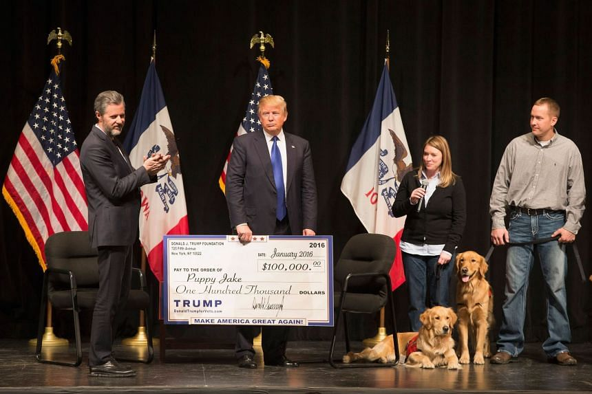 Donald Trump presents a cheque from the Trump Foundation to the Puppy Jake on Jan 30, 2016 in Davenport, Iowa.