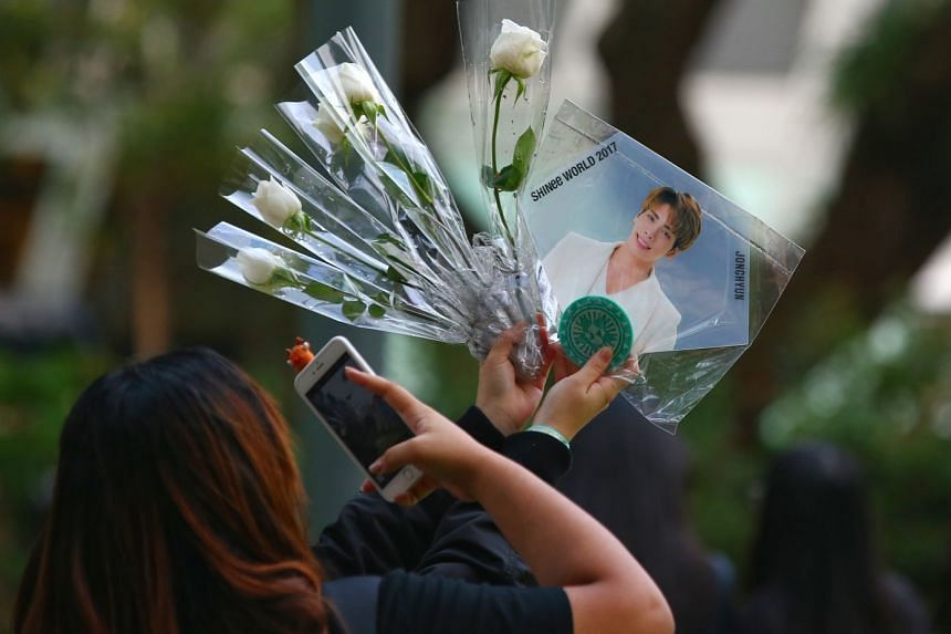 A fan taking photos of a picture of Shinee's lead singer Jonghyun at a memorial service held for him at Hong Lim Park in Singapore last year.