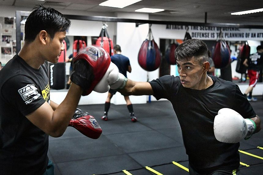 Mohammed Narish Mohamed Noh (at right) being coached by three-time SEA Games bronze medallist Muhamad Ridhwan during a training session, under The Chosen Wan (TCW) Cares Programme, which provides free membership for at-risk youth to train at Ridhwan'