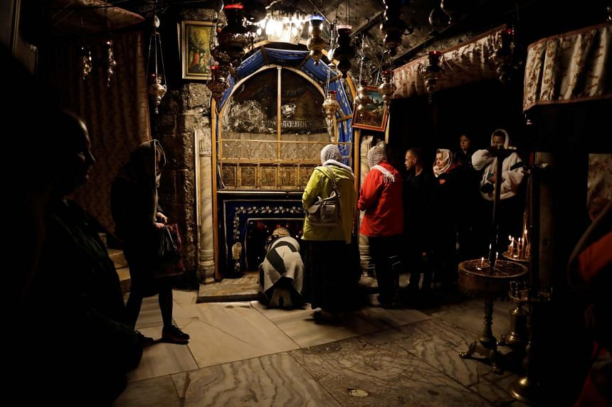 A group of tourists and pilgrims at the Grotto, believed to be the exact spot where Jesus Christ was born, at the Church of the Nativity in  Bethlehem on December 12, 2018.
