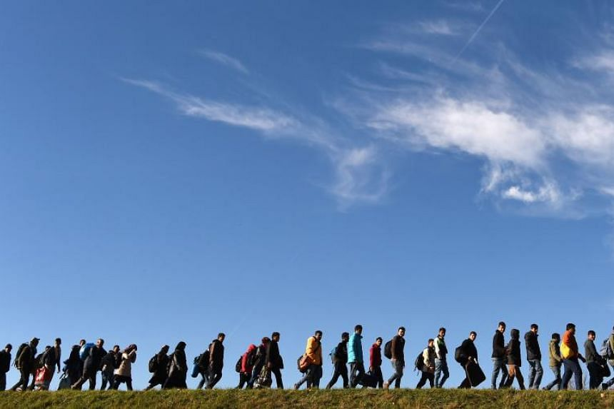 Migrants walk to a first registration point of the German federal police after they crossed the Austrian-German border in the small Bavarian village of Simbach, southern Germany, on Nov 2, 2015.