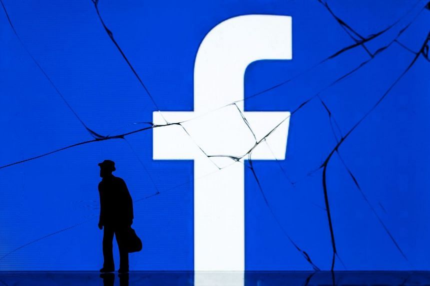 A figurine standing in front of the logo of social network Facebook on the cracked screen of a smartphone.