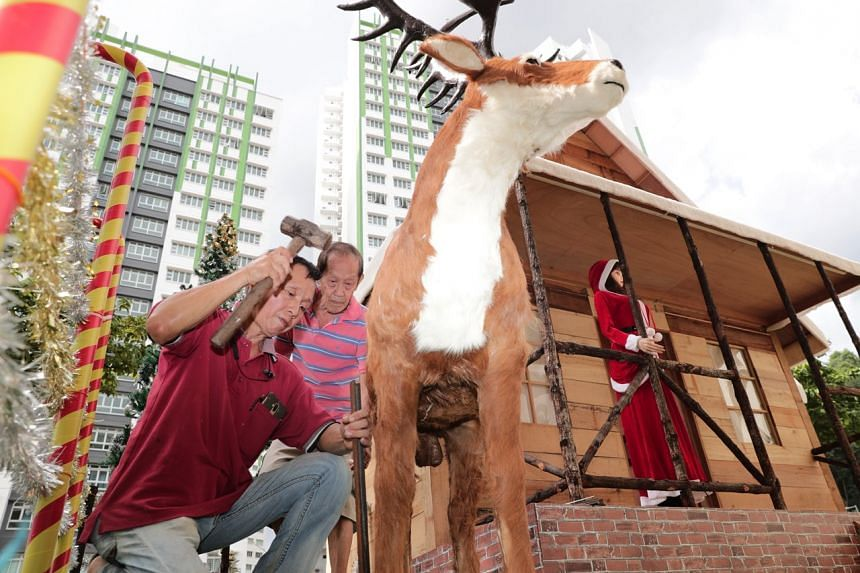 Mr Tan Koon Tat fastening a reindeer figure to the ground with help from his neighbour.
