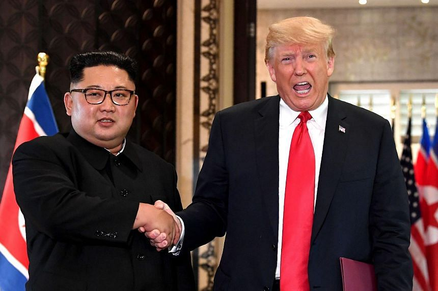 President Donald Trump and North Korea's leader Kim Jong Un shake hands following a signing ceremony during their historic US-North Korea summit, on June 12, 2018.