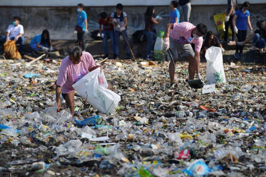 Volunteers pick up trash along Manila Bay for World Coastal Clean Up Day in Manila on Sept 22, 2018.