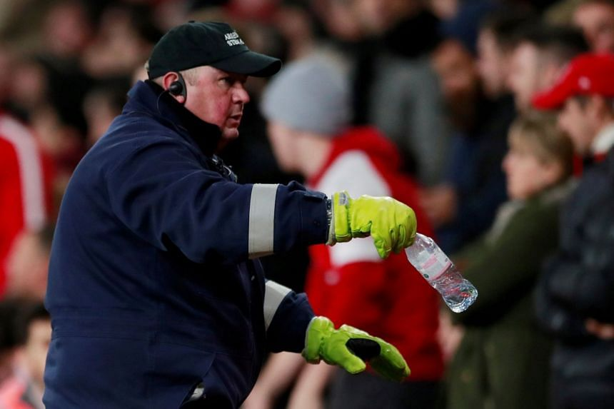 A security staff member removes the bottle from the pitch that hit Tottenham's Dele Alli.