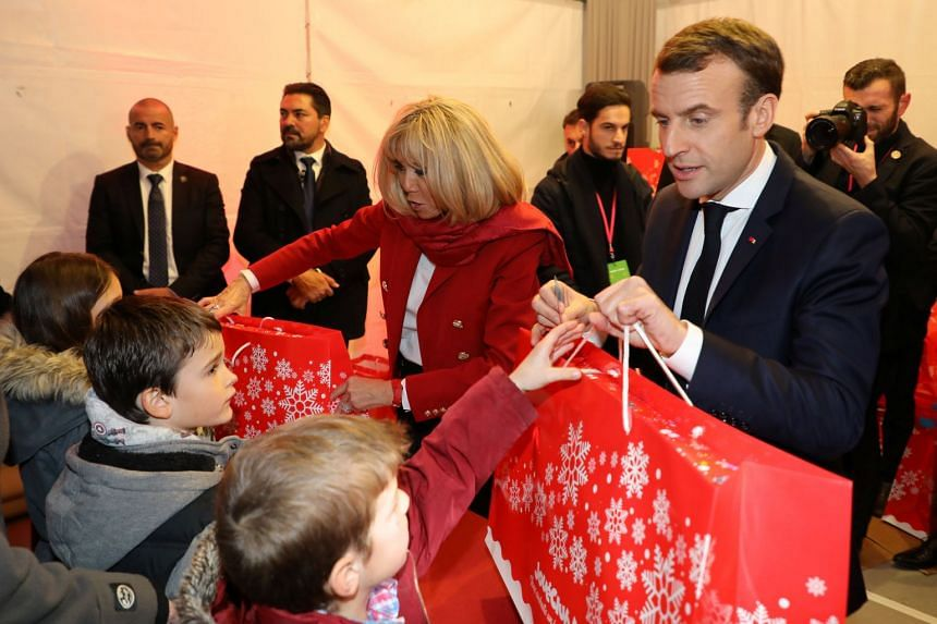 French President Emmanuel Macron and his wife Brigitte give presents to children during the Christmas Party for the children of Elysee Palace's employees in Paris on Dec 19, 2018.
