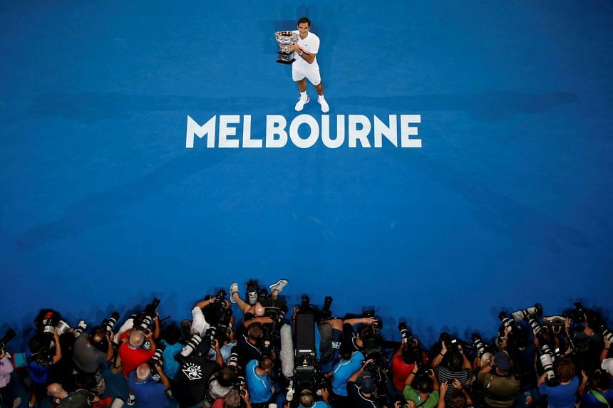 Roger Federer poses with the Australian Open trophy after winning the final at the Rod Laver Arena in Melbourne on Jan 28, 2018.