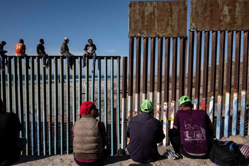 Migrants from Central American countries are seen near the US border in Playas de Tijuana, Mexico.