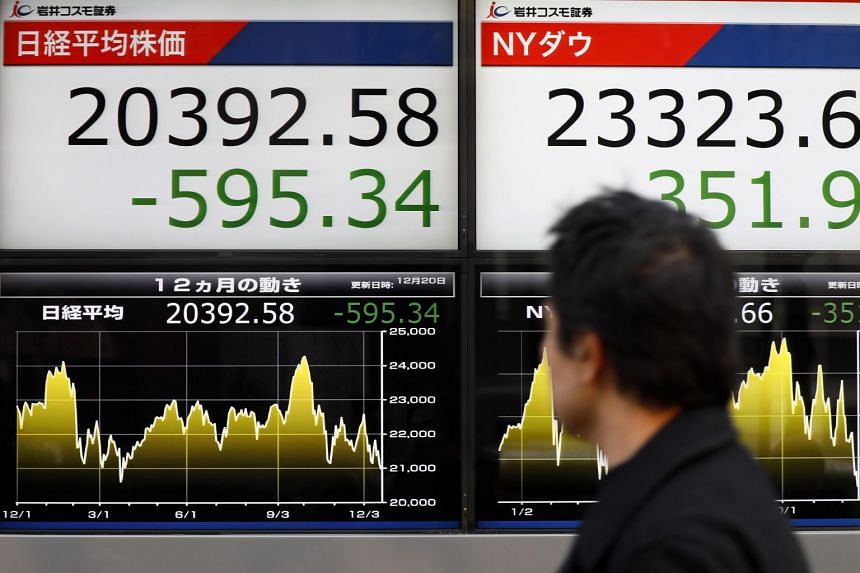 A pedestrian walks past a display showing closing information of Tokyo benchmark Nikkei Stock Average, after Wall Steet's loss, in Tokyo, Japan on Dec 20, 2018.