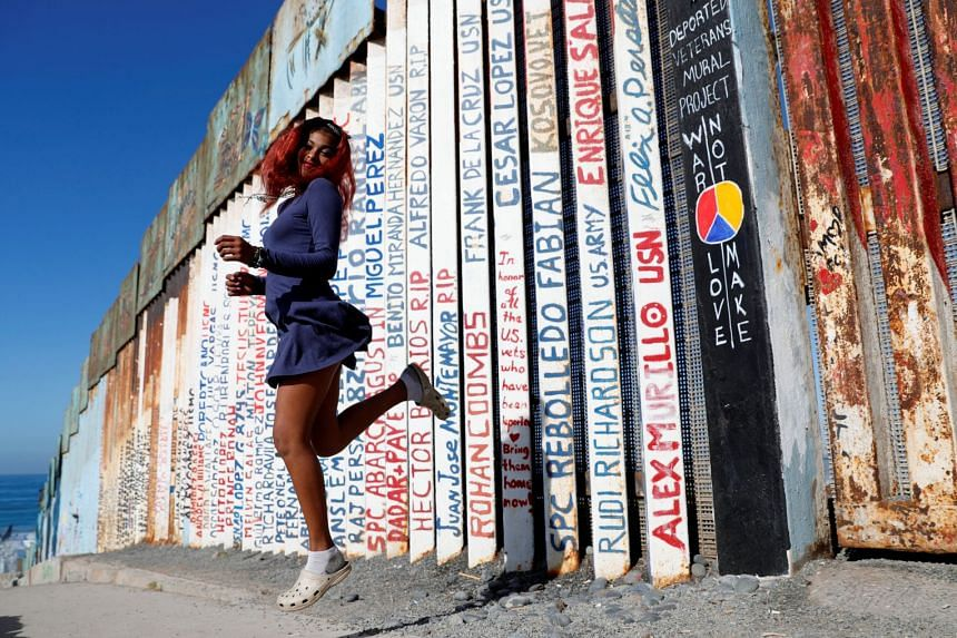 Yaderin Alexandra Banias, a migrant from Honduras, poses in front of the border wall between the US and Mexico.