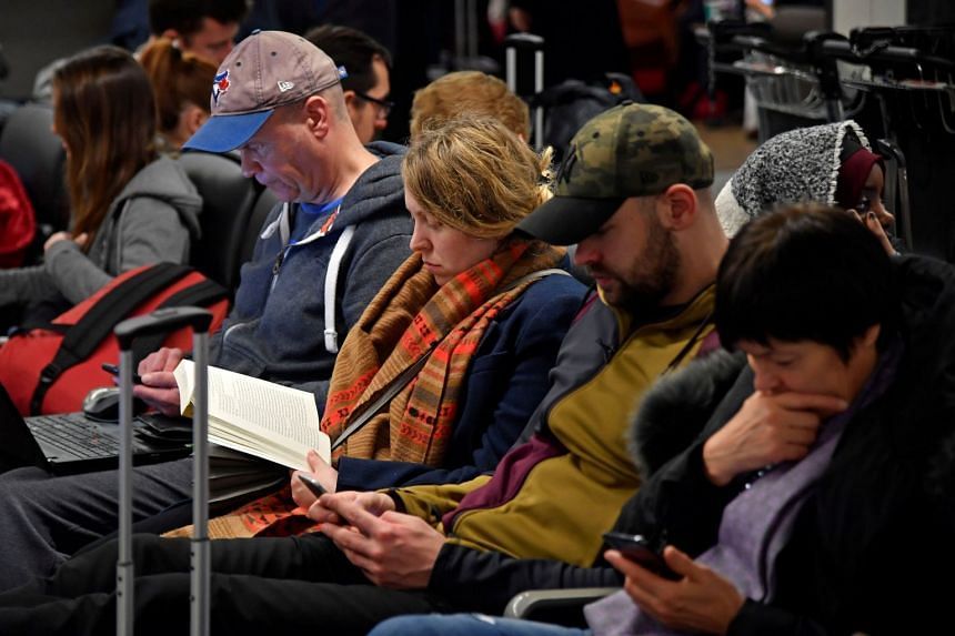 Passengers wait in the South Terminal building at Gatwick Airport, after the airport reopened to flights following its forced closure because of drone activity.