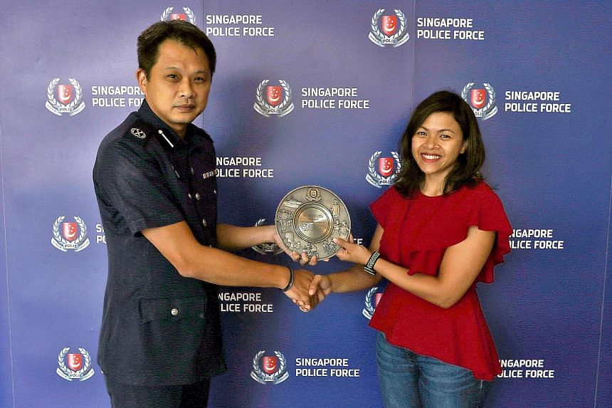 Deputy Commander of Airport Police Division Goh Wee Khern presenting the Public Spiritedness Award to Ms Kanya yesterday.