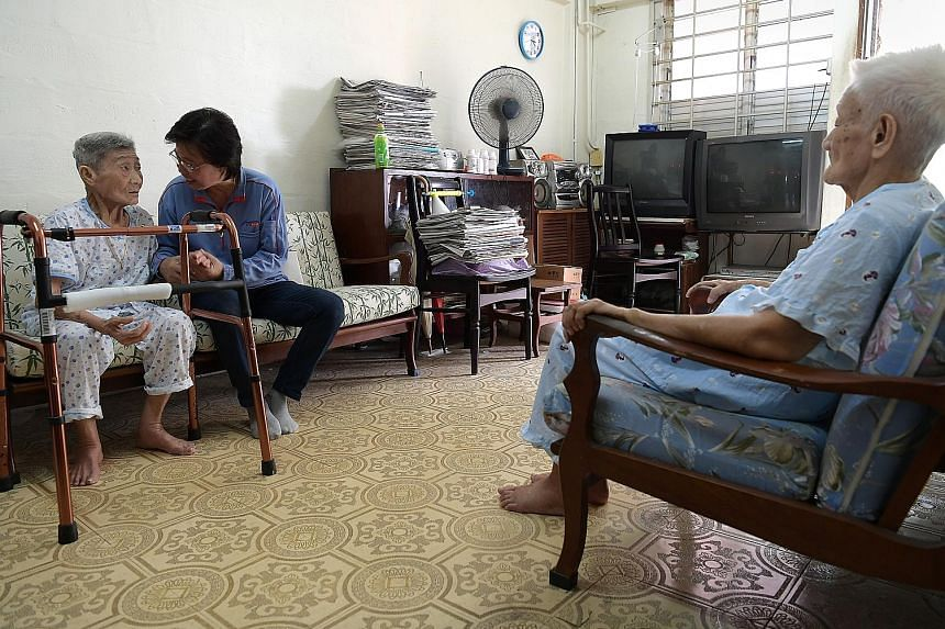 Postman Seah Seow Peng looks in on sisters Thi Lai Lee (left) and Teh Lai Wam at least once a week. Both elderly women have dementia.