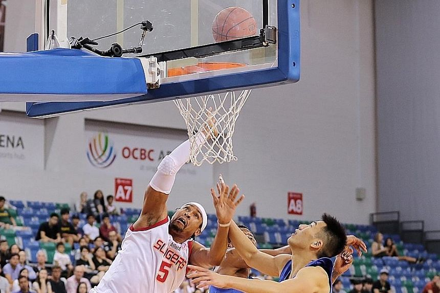 Singapore Slingers centre John Fields trying to score despite the close attention of two Hong Kong Eastern players in their Asean Basketball League match at the OCBC Arena last night.