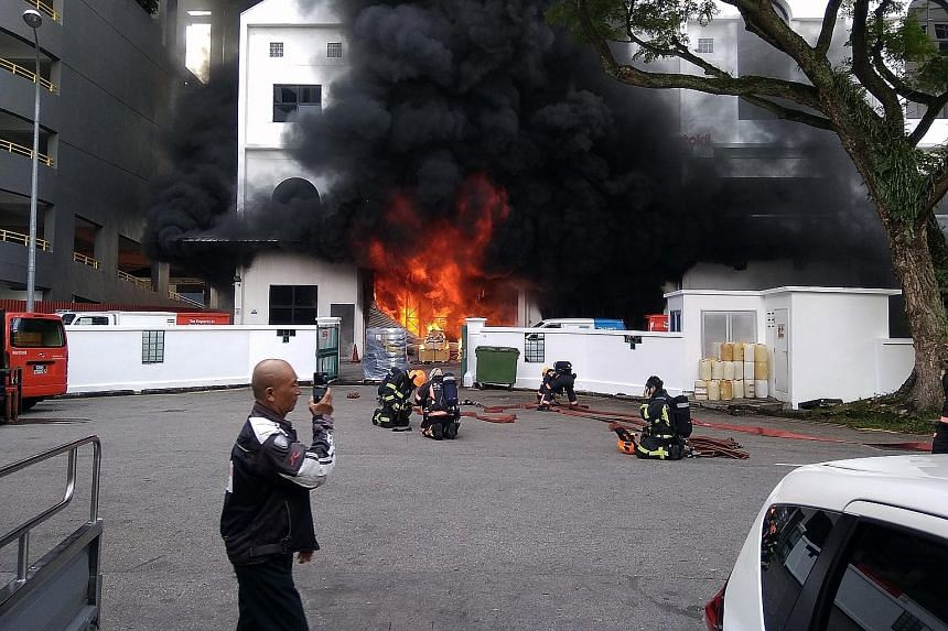 As the fire raged (above) at the headquarters of pest control company Rentokil Initial Singapore in MacPherson yesterday morning, dark dense smoke could be seen billowing from the building hundreds of metres away. About 45 firefighters (right) were d