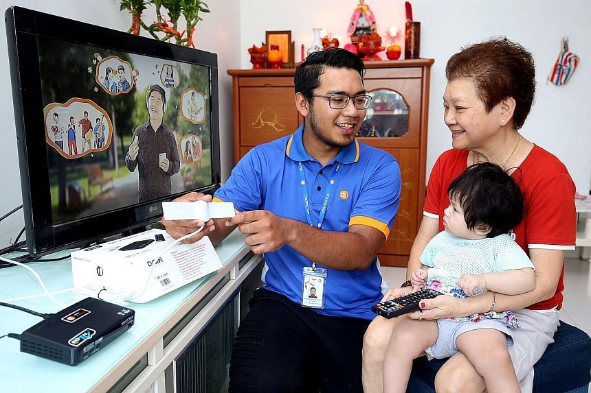A vendor installing a digital tuner and antenna for an HDB household. All HDB households that do not have a pay-TV subscription are eligible for the government-sponsored kits.