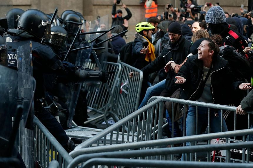 Catalonia's local police force keeping protesters behind crowd control barricades during a Catalan pro-independence demonstration in Barcelona yesterday. Spanish Prime Minister Pedro Sanchez brought a weekly Cabinet meeting to Barcelona, triggering p