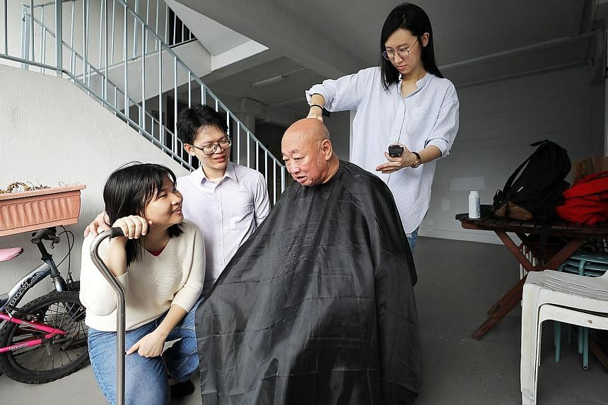 Ms Poh Chu Yin giving Mr Yeo Yeo Hong a haircut outside his flat, as volunteers Abraham Yeo and Peng Chengyu, 23, a nurse, talk to the 76-year-old retiree.
