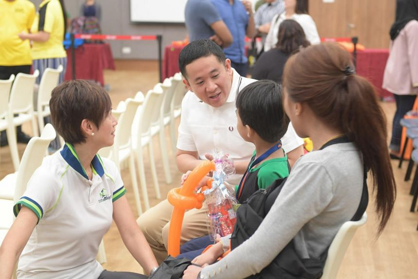 Senior Parliamentary Secretary for Home Affairs Amrin Amin and Manpower Minister Josephine Teo chat with a family during the launch event for the Back To School initiative at Heartbeat@Bedok on Dec 22, 2018.