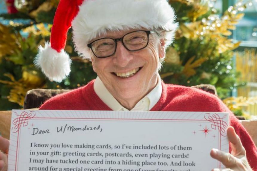Microsoft co-founder Bill Gates posing with a message he gave to a Redditor for this year's Christmas along with lots of presents. For a number of years, Mr Gates has been a participant in redditGifts, an online Secret Santa game held via social we