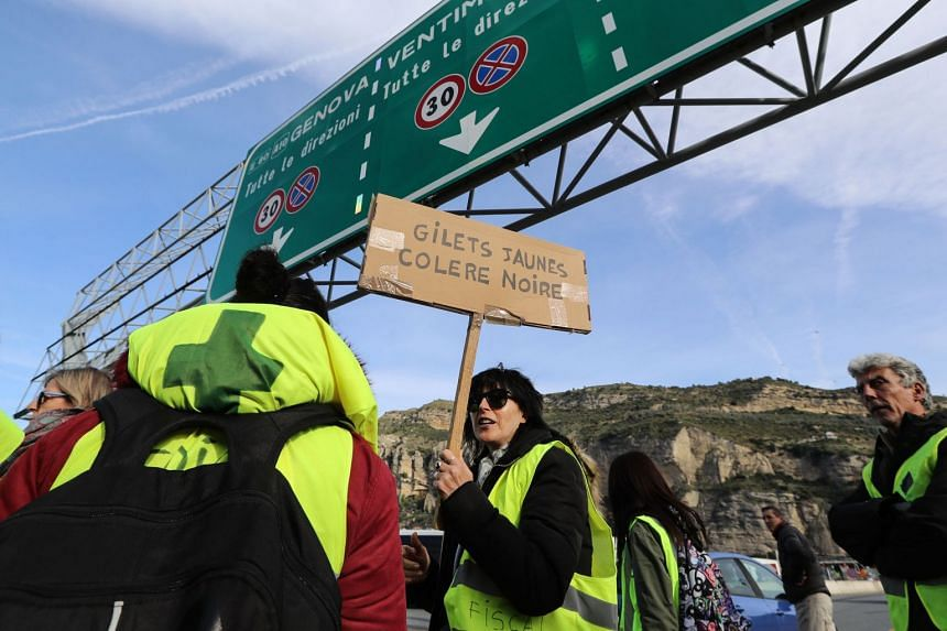A protester holds a placard reading 'yellow vests, in a rage' in Ventimiglia near the French-Italian border.