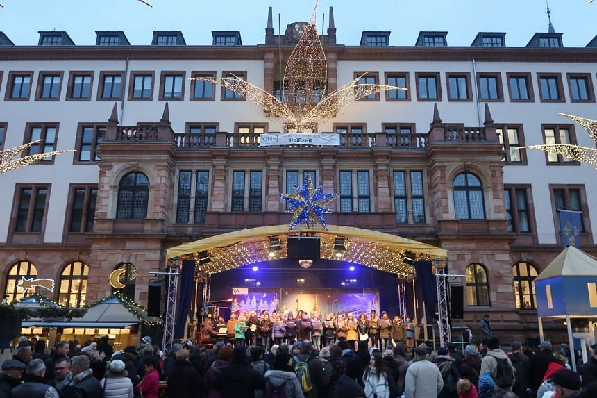 A local choir singing in a mediaeval square, at one of Germany's annual Christmas market.