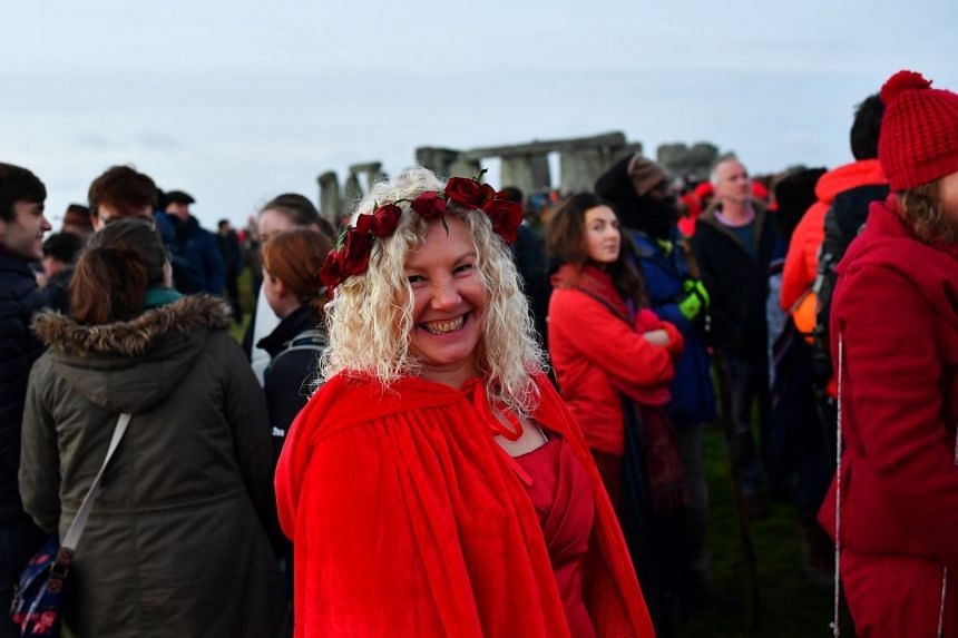 The sun rises as revellers welcome in the winter solstice at Stonehenge.
