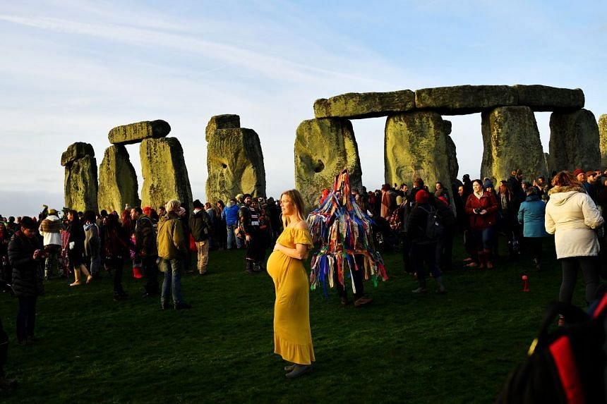 Ann Bloom, from Canada, joins revellers as they welcome in the winter solstice at Stonehenge.