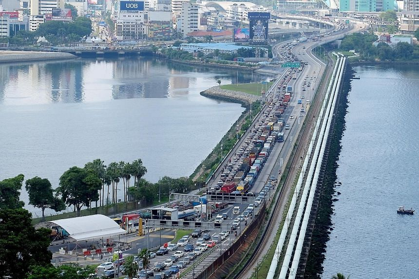 Left: While there were still jams, the traffic situation at the Causeway yesterday was far better than last week, with shorter waiting times for motorists heading north. Above: The two ICA officers were filmed allegedly hitting a truck driver on Frid