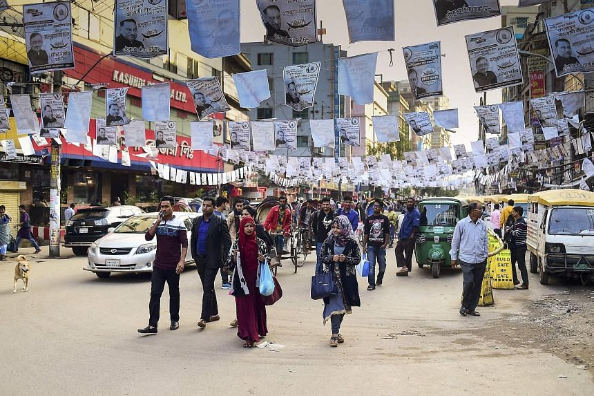 Posters of the ruling Awami League's candidates hanging over a street in Dhaka last Friday. Bangladesh goes to the polls on Dec 30.