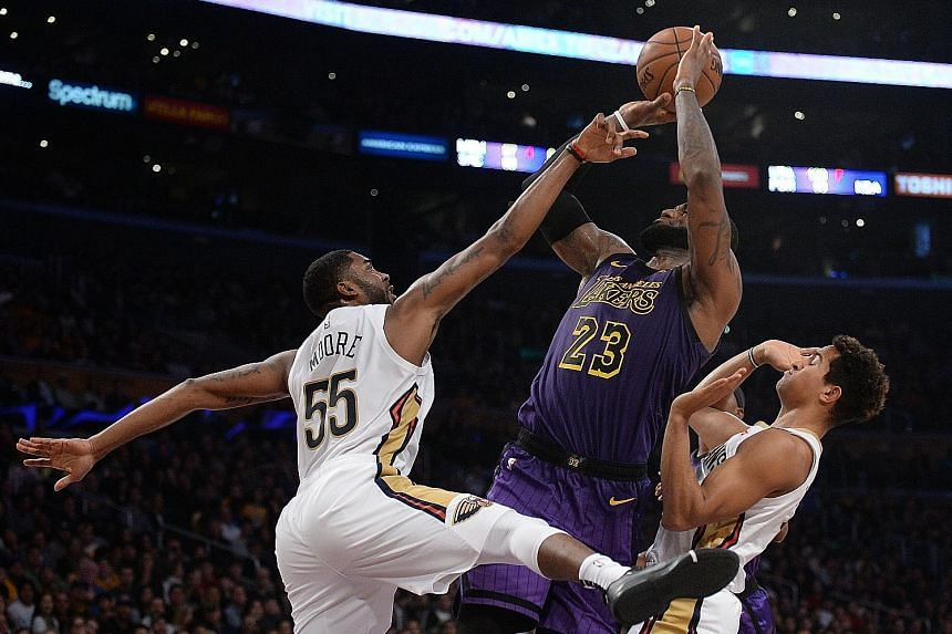 LeBron James shooting between New Orleans Pelicans guards Frank Jackson (left) and E'Twaun Moore at Staples Centre. The Los Angeles Lakers forward showed flu-like symptoms at the start but still posted his third triple-double of the season. The Laker