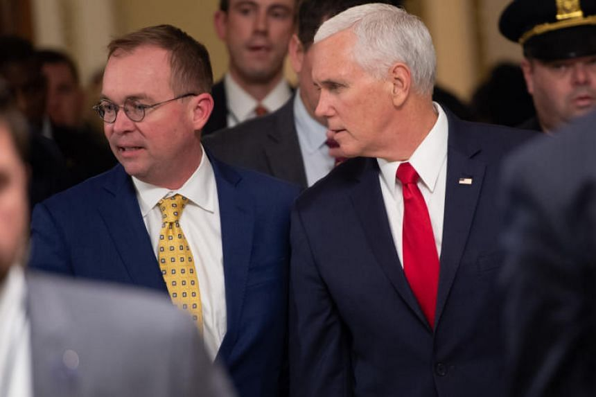 US Vice President Mike Pence and Mick Mulvaney (left), Director of the Office of Management and Budget and incoming White House Chief of Staff, walk between meetings to discuss a possible government shutdown, at the US Capitol in Washington, DC, on D