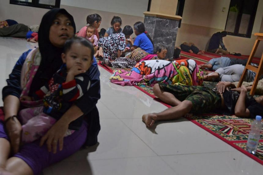 Residents sit inside a mosque as they evacuated following high waves and the eruption of Anak Krakatau volcano at Labuan district in Pandeglang regency, in Indonesia on Dec 22, 2018.