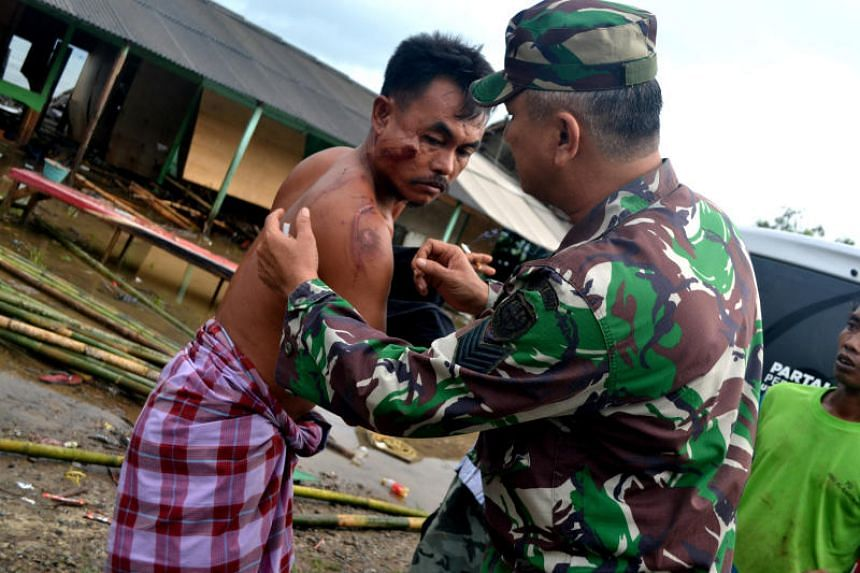 A soldier examines a local resident's injuries following a tsunami which hit the Tanjung Lesung district in Pandeglang, Banten province, Indonesia, on Dec 23, 2018.