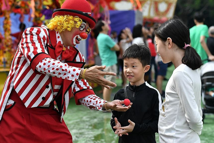 A clown entertaining siblings An Jongwon, eight, and An Jeeyoon, 11, with a magic trick at the carnival.